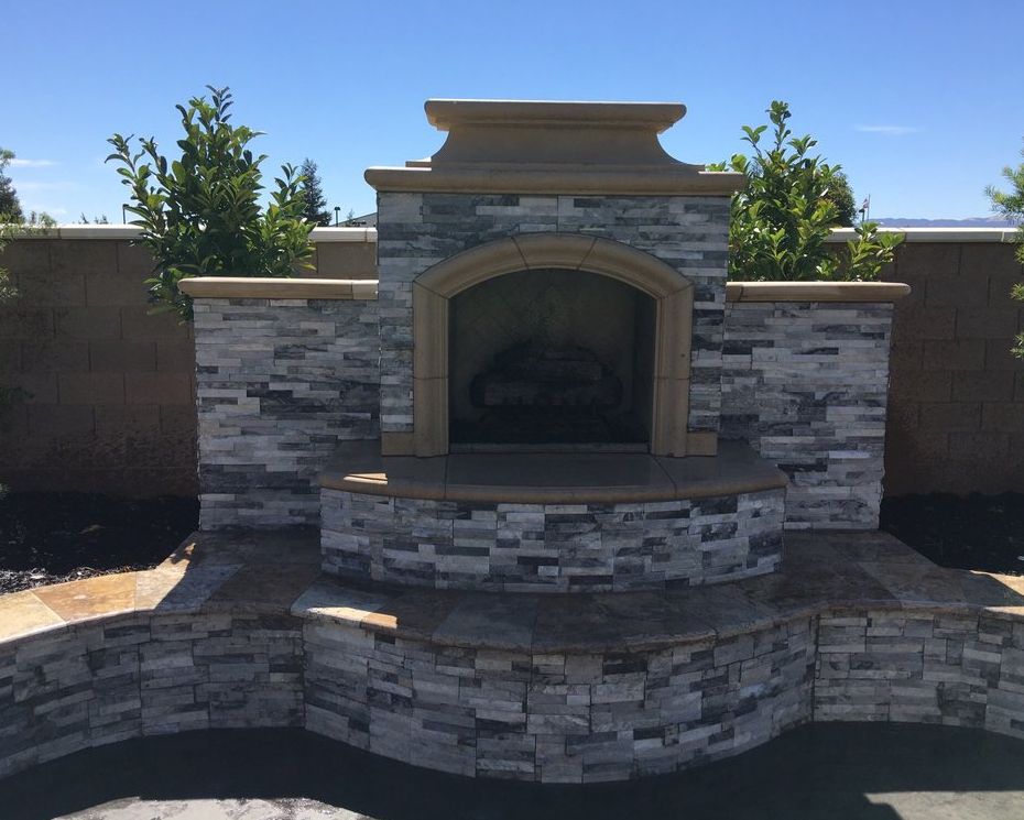 a picture of a stacked stone fireplace with a stamped concrete patio and sitting area in Modesto, California